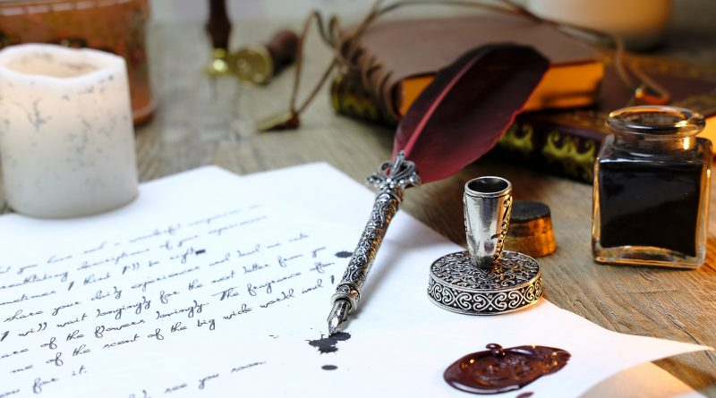 Tintenklecks und Schreibfeder auf einem Blatt Papier