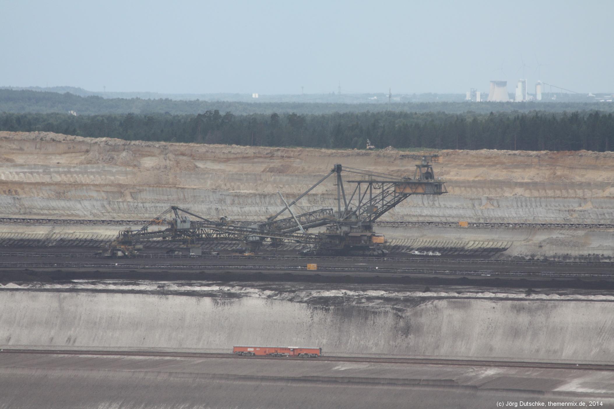 Ein kleiner Waggon unterhalb eines riesigen Abraumbaggers im Tagebau Nochten